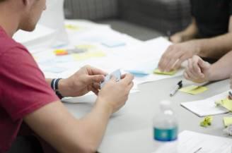 Personen am Tisch arbeiten mit Zetteln und Stiften