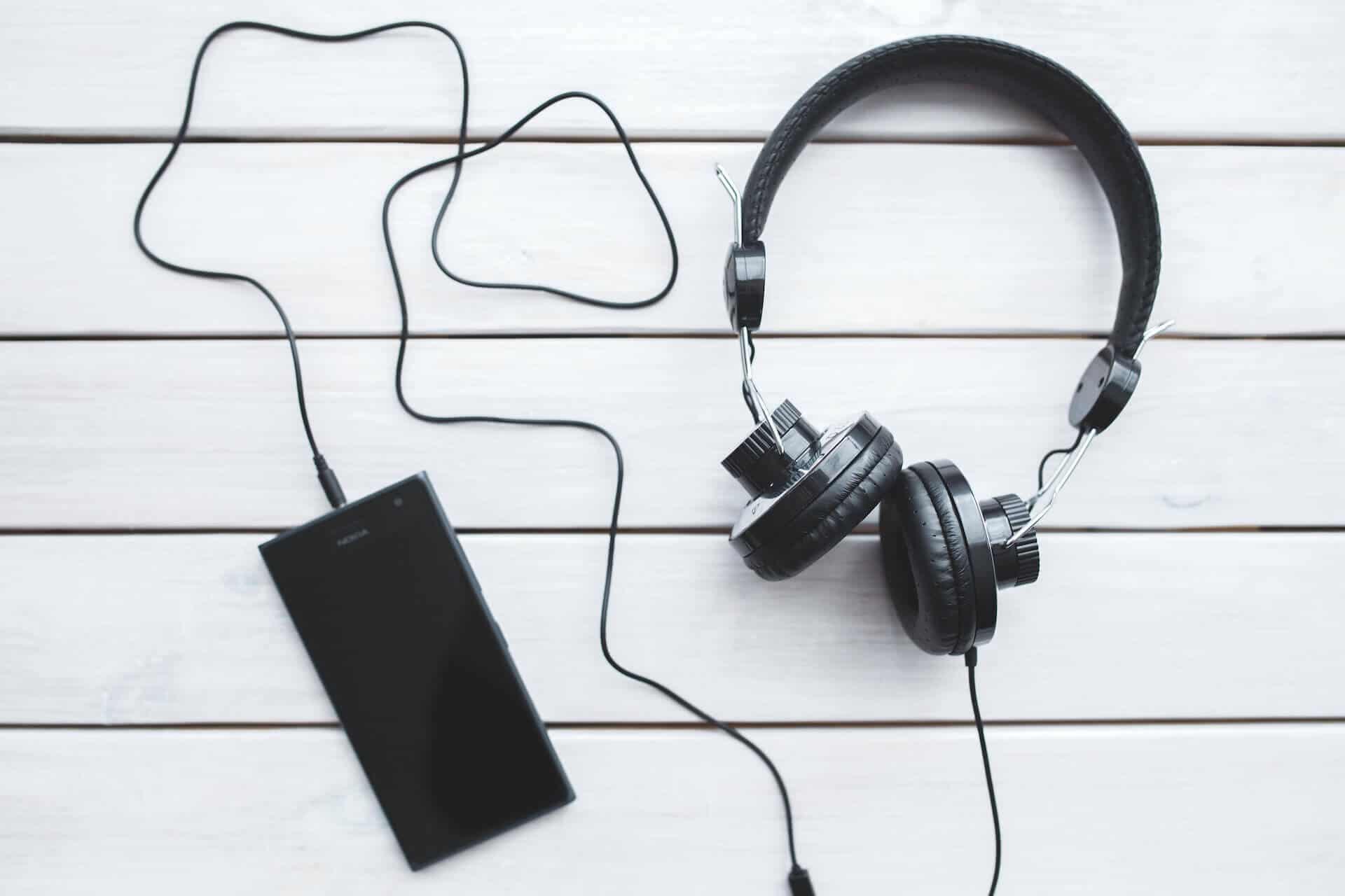 Smartphone auf Tisch mit Audiokabel und Kopfhörer