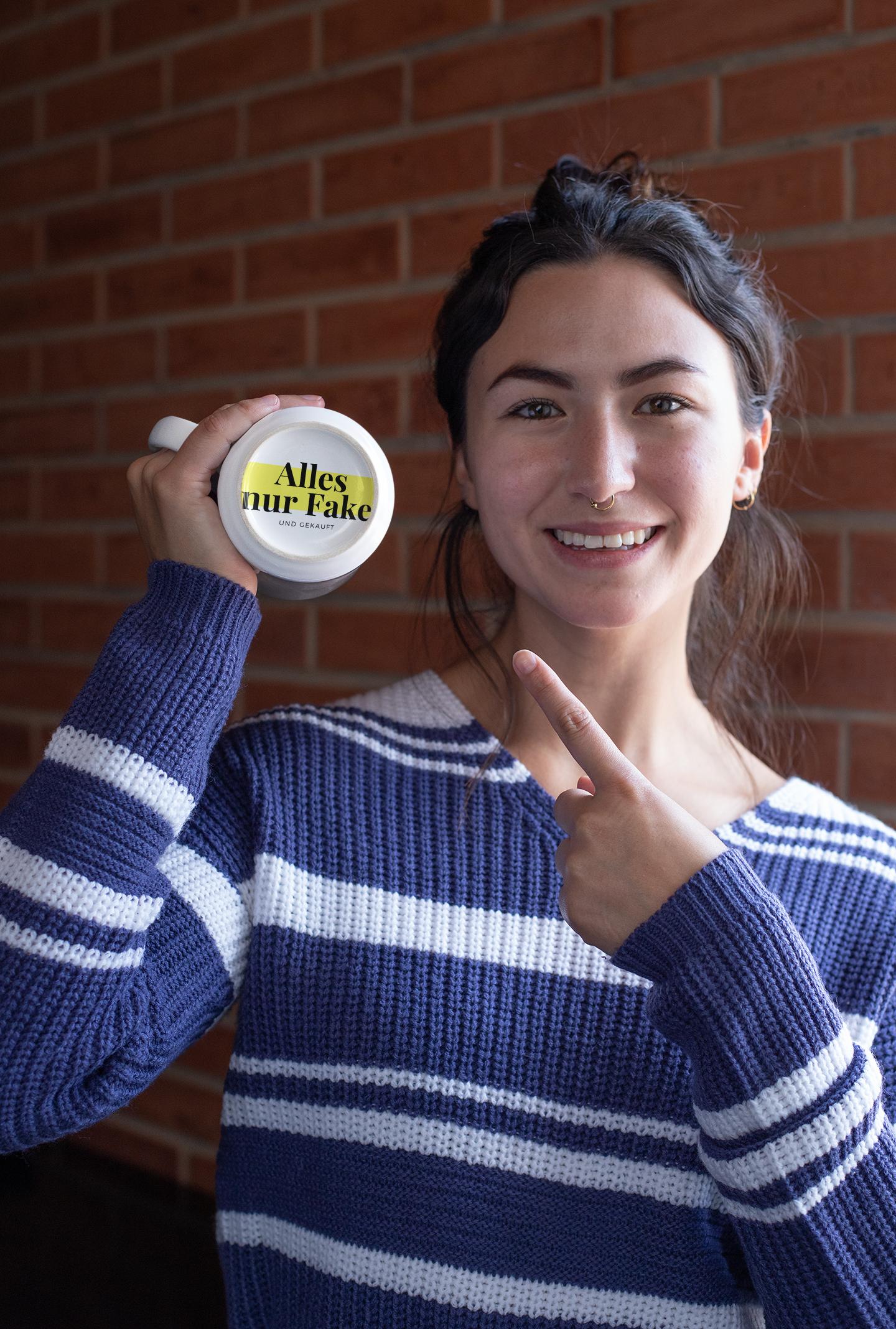 """Frau zeigt Tasse mit Logo """"Alles nur Fake"""""""