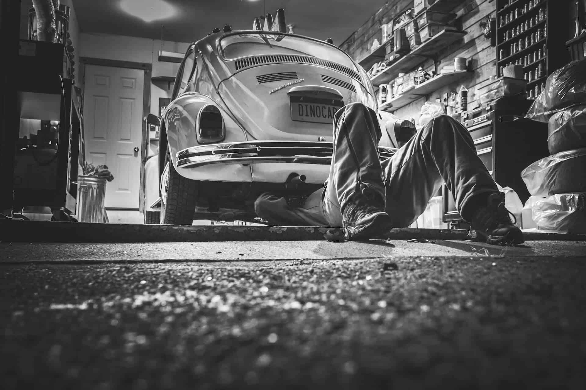 Mann in Autowerkstatt checkt Auto