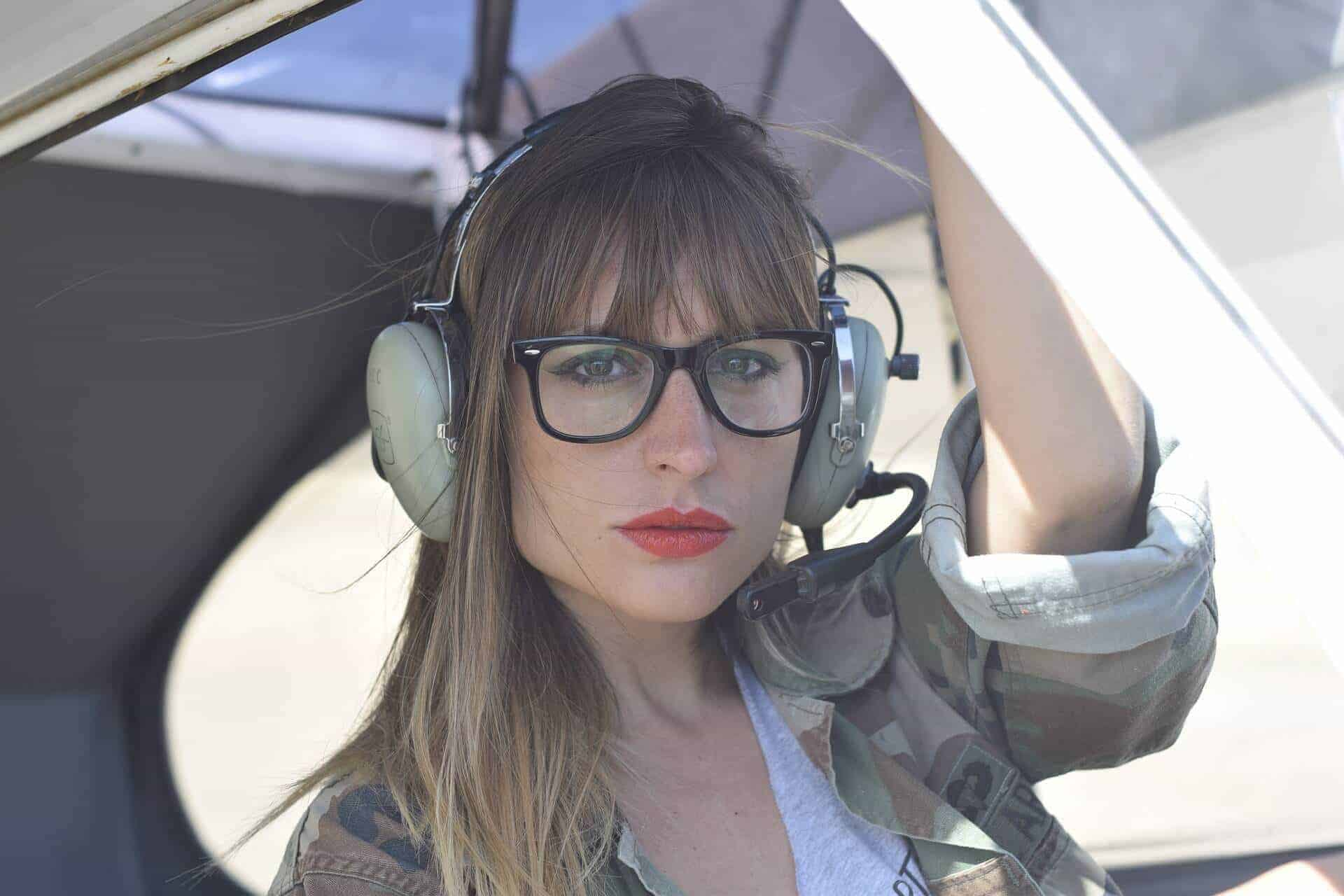 Pilotin mit Kopfhörer in Flugzeug