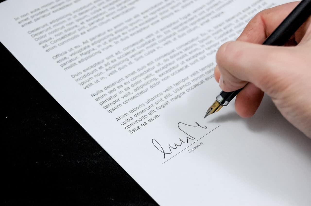 Person unterschreibt Vertrag mit Stift