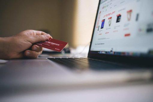 Hand mit Kreditkarte beim Kaufen mit Notebook im Internet