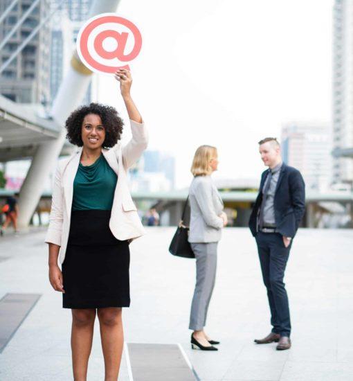 Person zeigt lächelnd das Zeichen @ als E-Mail-Symbol