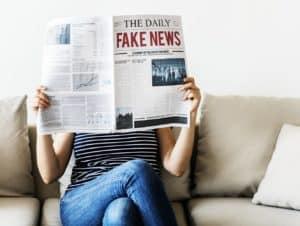 Frau mit Zeitung, Titel: The Daily Fake News